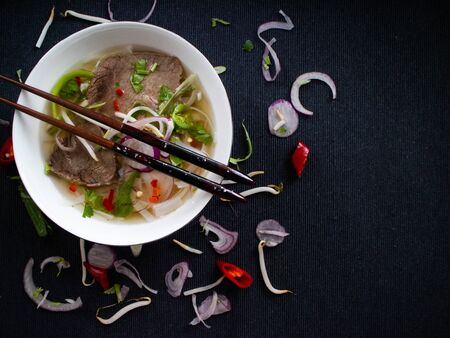 Beef soup from Vietnam with wooden chopsticks and peppers