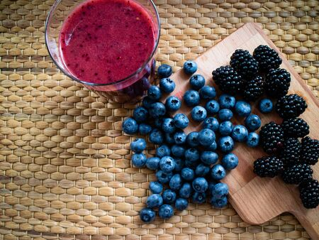 Red smothie with some blueberries and blackberries on a table Stok Fotoğraf