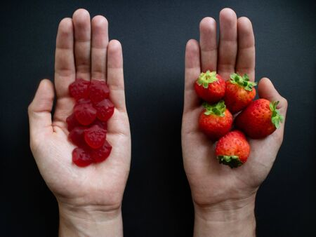 Healthy strawberries vs unhealthy strawberry candies. Top view of man´s hands holding fresh fruit and sweets
