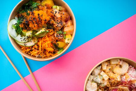 Flat lay composition with prawn poke and salmon poke on a blue and pink background with chopsticks