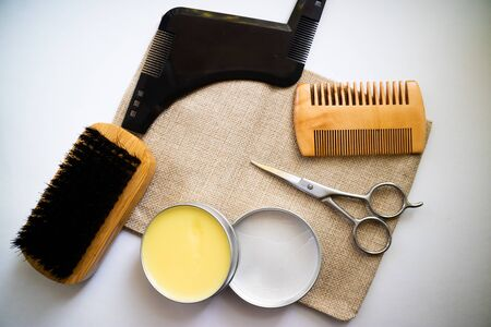 Expert beard care supplies such as comb, brush, scissor and wax made from natural ingredients. Flat lay on a white background.