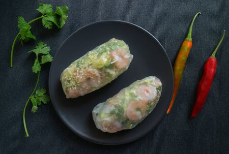 Summer rolls on a plate with peppers and coriander