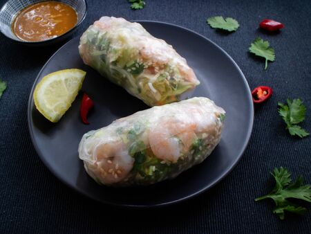 Summer rolls on a plate with lemon, coriander, peppers and sweet and sour sauce to dip.