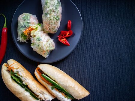 Banh mi heo nuong with summer rolls on a plate server with peppers