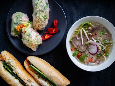 Vietnamese soup, sandwich and summer rolls on a dark background.