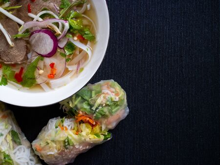 Pho bo soup with cilantro and other vegetables, served with summer rolls on a gray background