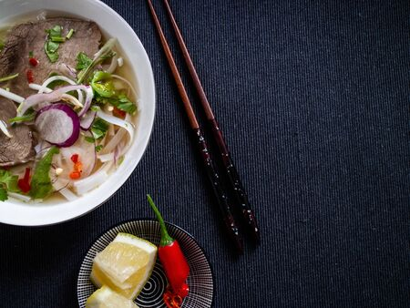 Vietnamese food pho bo with lemon, peppers and traditional wooden chopsticks