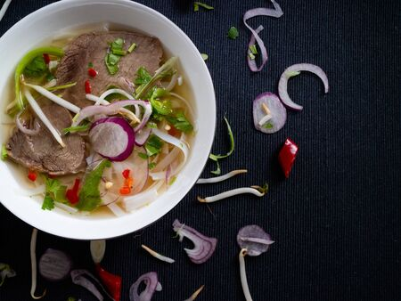 Traditional beef soup from Vietnam pho bo garnished with pepper, onion, coriander and soybeans