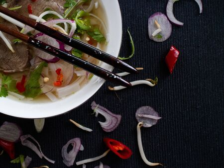 Chopsticks on a plate filled with pho bo and garnished with vegetables and soybeans Stok Fotoğraf