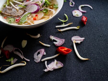 Pho bo on a gray background with peppers, soybeans and red onion