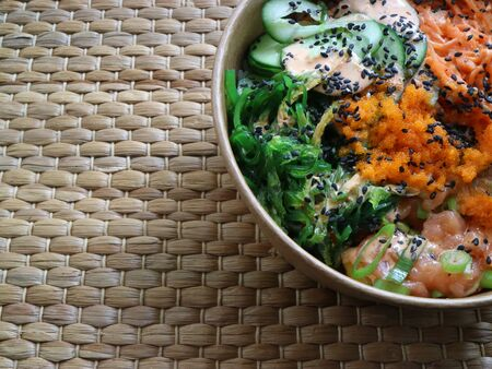 Poke with salmon, wakame and other tropical ingredients in a bowl