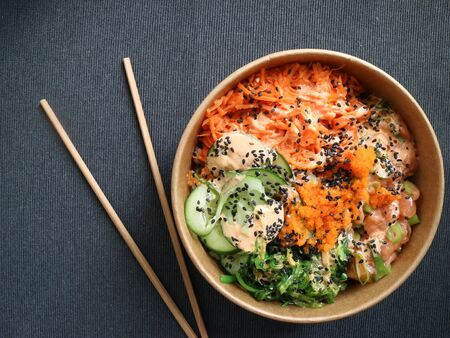 Poke with brown rice and salmon on gray background.