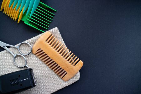Flat Lay of barber tools, scissors, comb, electric razor and heads on dark background. Copy space