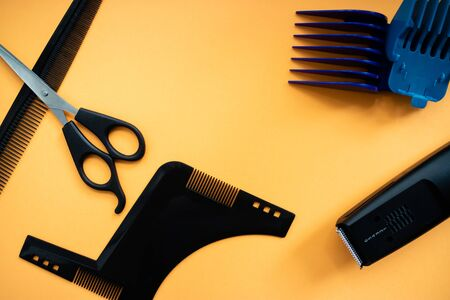 Barber set with scissors, comb, electric razor and heards on yellow background. Flat lay