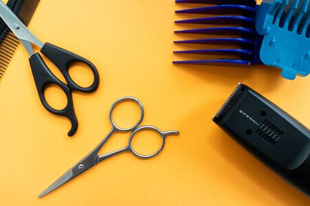 Top view of scissors, and trimmers for hair and beard on orange background. Stock Photo