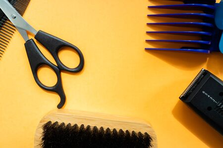 Different combs and tools for beard grooming on orange background. Flat lay