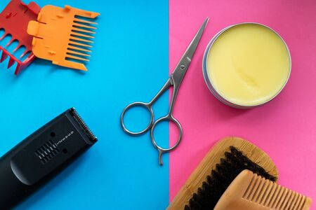 Beard set, scissors, comb, brush, shaver and wax on blue and pink background. Flat lay