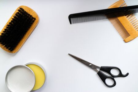 Brushes and wax for beard grooming on white background.