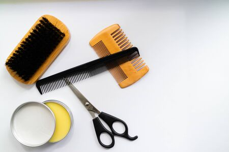 Scissors, brush, comb and wax gor beard grooming. Flat lay with copy space.