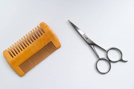 Comb and scissors isolated on white background.
