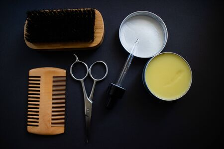 Beard grooming kit with comb, brush, scissor, wax and balm. Flay lay on a black background