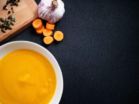 Pumpkin cream with some pieces of carrot and garlic in a gray background