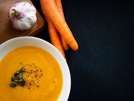 Homemade vegetable soup made with seasonal products like carrot and pumpkin
