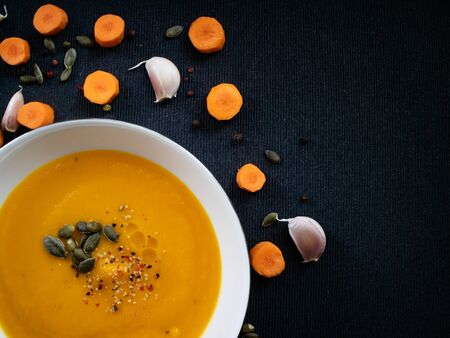 Top view of a white plate with vegetable soup made of carrot and pumpkin