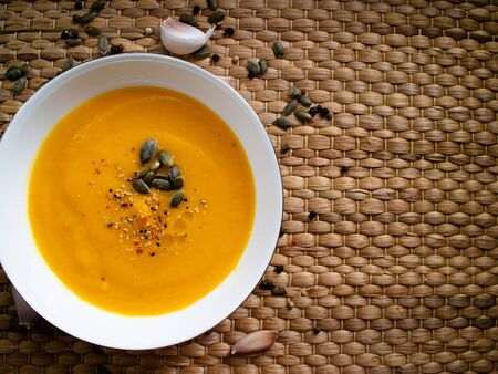 Vegetable cream made with carrot and pumpkin on a wicker background Stock Photo