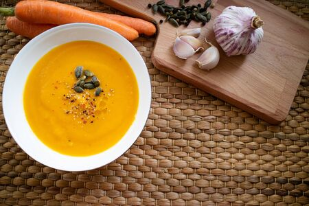 Vegetable cream ready to eat with carrot, garlic cloves and pumpkin seed as background Imagens