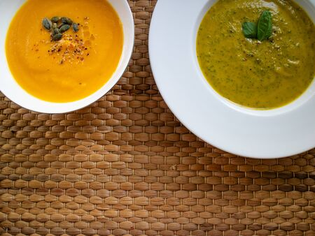 Carrot and pumpkin cream with spinach soup or wooden background.