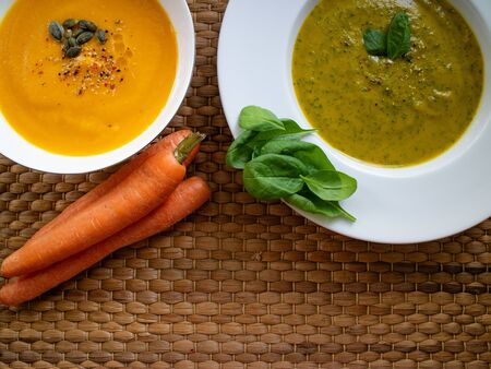 Spinach and courgette cream with carrot and pumpkin cream with some carrots on a wooden background.