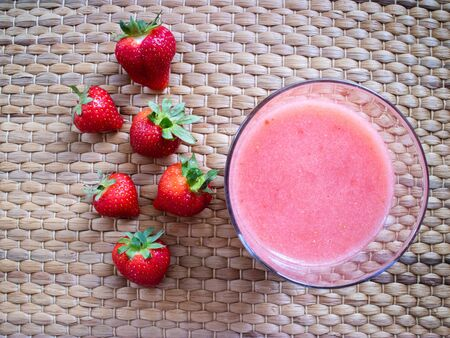 Top view of a strawberry smothie on a glass with wooden background.