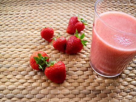 Strawberry smothie on a glass with wooden background