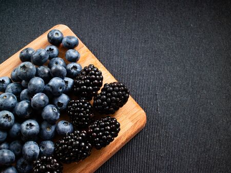 Table with wildberries such as strawberrries, blueberries and raspberries with a smothie. Top view Stock Photo