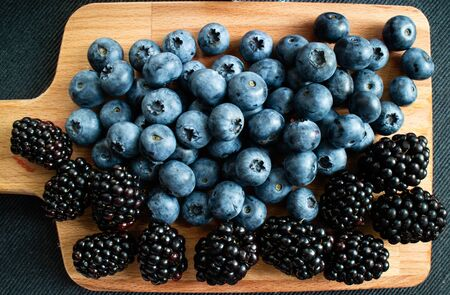 Wooden table with some blueberries and blackberries. Top view