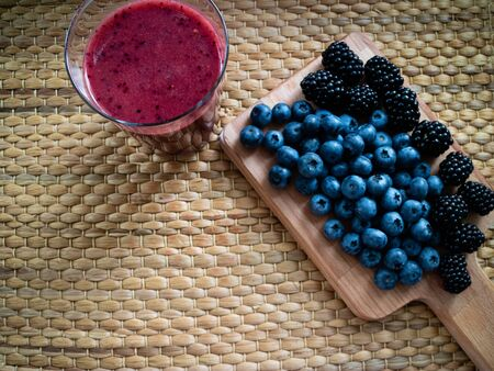 Table with blueberries and blackberries with a red smoothie on wooden background. Stock Photo