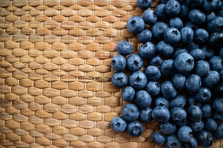 Fresh and organic blueberries on a wicker background. Top view picture with copy space.