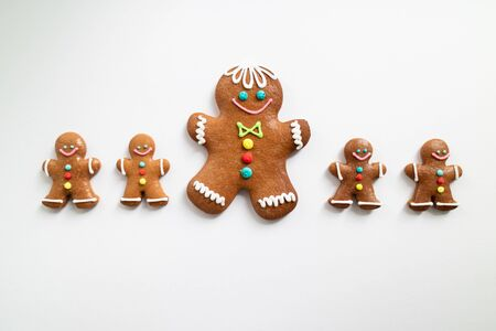Line of different sizes of Gingerbread men isolated on white background. Christmas tradition Top view