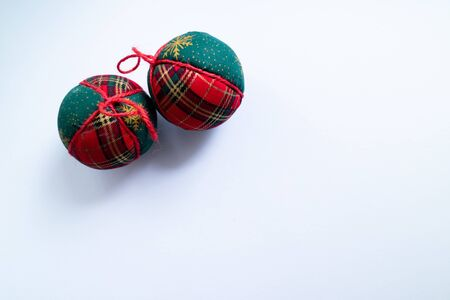 Christmas balls with traditional red and green winter print on white background.