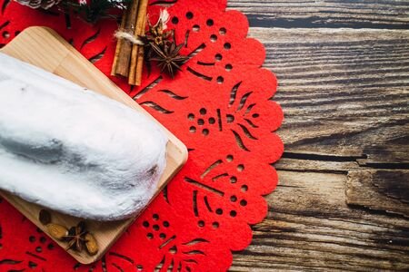 German stollen with ginger, cinnamon, raisins and orange on Christmas background. Top view Banco de Imagens