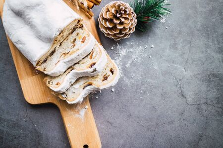 Top view of a stollen cake and some slices on a wooden table. Christmas recipe Banco de Imagens