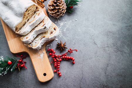 German stollen with orange, raisins and anise on Christmas background. Top view Banco de Imagens