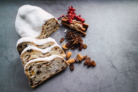 Christmas stollen and some slices on concrete background.