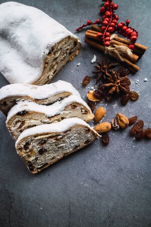 Christmas stollen with almonds, raisins, anise and cinnamon on concrete background. Blogging concept. Vertical picture