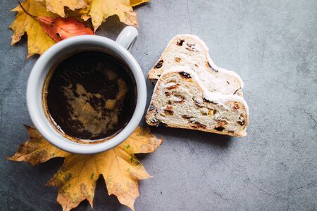 Cafe latte and Christmas stollen on concrete background with some autumn leaves.