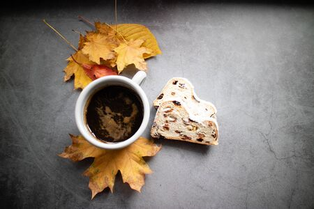 German stollen and mug of coffee on an autumn leaves. Banco de Imagens