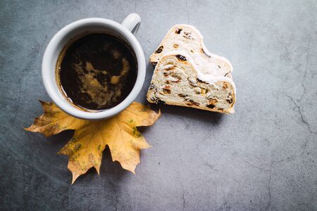 Top view of a cup of coffee and two stollen slices on concrete background. Archivio Fotografico - 138043271