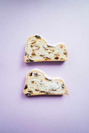 Two stollen slices on purple background. Blogging concept. Christmas cake