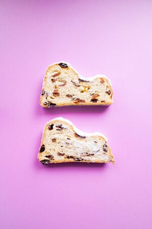Two stollen slices on pink background. Blogging concept. Christmas cake Banco de Imagens